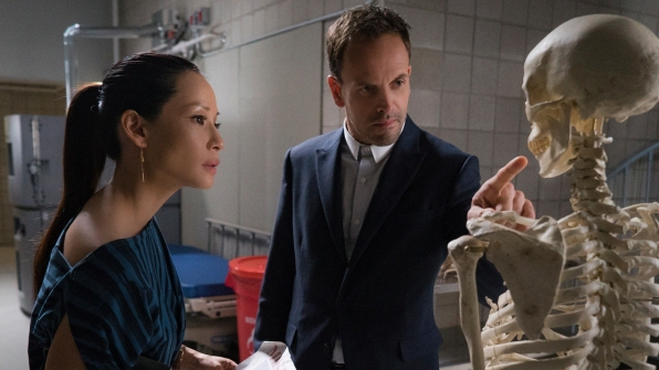 Joan Watson (Lucy Liu) and Sherlock Holmes (Jonny Lee Miller) inspect a skeleton that might belong to their suspect's latest victim. Photo by CBS.